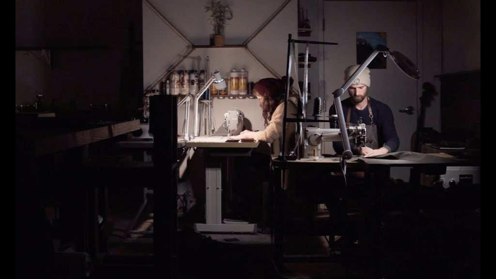 two people sewing and working on leather products at uphill designs in seattle